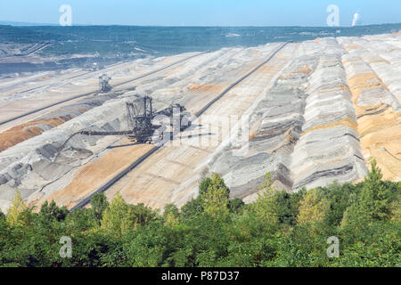 Brown coal open pit landscape with digging excavators in Germany - Stock Photo