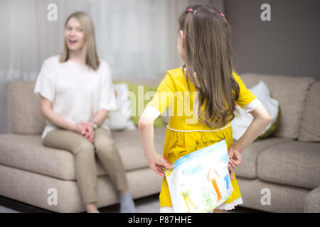 Child daughter congratulates mother and gives her painting. Mother and girl smiling and hugging. Happy mother's day! - Stock Photo