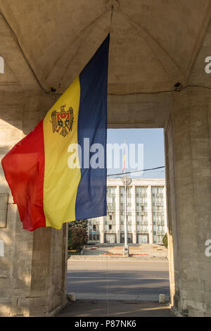 Flag of Moldova waiving under the Triumphal Arch (Arcul de Triumf) in dowtown Chisinau (Kishinev), in front of the Government House. The Arch is one o - Stock Photo
