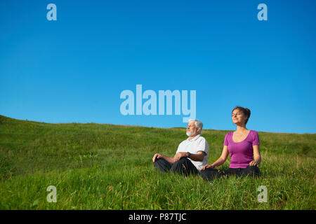 Two people meditating sitting in the field. Sitting in lotus pose on bright saturated sky background. Looking positive, satisfied, feeling good, conce - Stock Photo