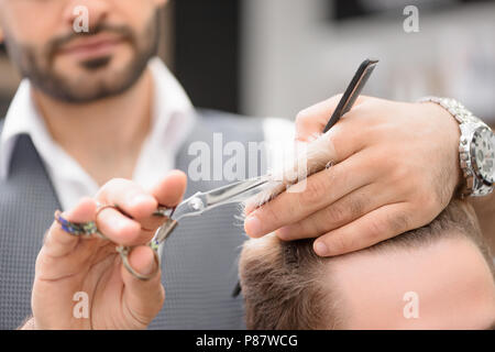 Photo of barber working with client in barbershop. Making professional haircut. Hairstyle looking fashionable, stylish. Hairdresser holding sharp scis - Stock Photo