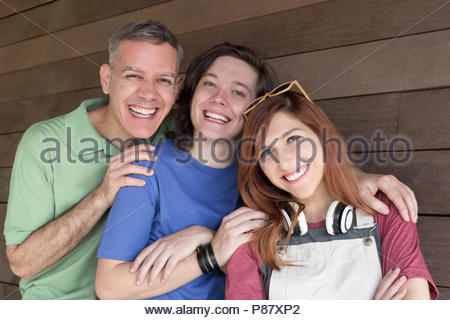 Portrait of Dad with teen daughter and son embracing each other and smiling. Father Day. Concept of family, enjoyment, fatherhood, fellowship, connect - Stock Photo