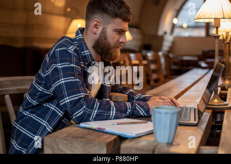 Young professional surfing the Internet on his laptop in a cafe - Stock Photo