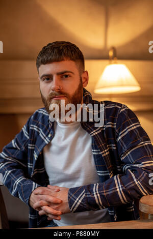 Portrait handsome bearded man wearing plaid shirt at modern cafe. - Stock Photo