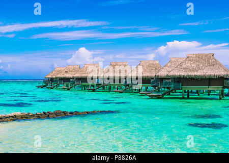 Luxury beach travel vacation concept: Overwater bungalows on turquoise coral reef lagoon ocean close to the beach. - Stock Photo