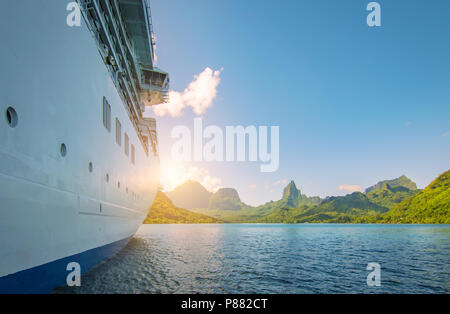 Side view of anchored cruise ship at sunset. Mountain background. - Stock Photo