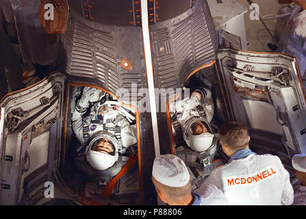 Astronauts L. Gordon Cooper Jr. (left) and Charles Conrad Jr. are seen in the Gemini-5 spacecraft in the white room at Pad 19 just after insertion - Stock Photo