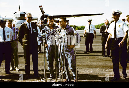 Astronauts John W. Young (left), pilot; and Virgil I. Grissom, command pilot, stand at microphones at the Cape's skid strip after being flown in from the recovery ship, USS Intrepid - Stock Photo