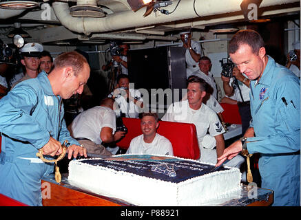 Astronauts Charles Conrad Jr. (left) and L. Gordon Cooper Jr. prepare to slice into the huge cake prepared for them by the cooks onboard the aircraft carrier USS Lake Champlain. - Stock Photo