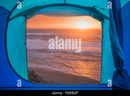 View from inside a tent onto a sunset over a beach and sea, Isle of Mull, Scotland. - Stock Photo