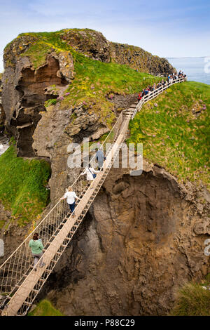 UK, Northern Ireland, Co Antrim, Ballycastle, Carrick-a-Rede island visitors on rope bridge - Stock Photo