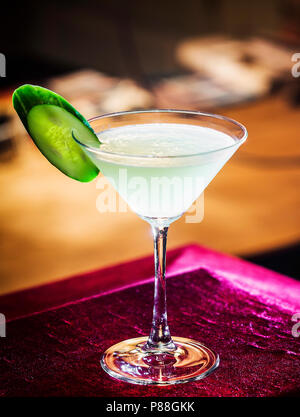 cucumber and lime martini mixed cocktail drink glass inside cozy bar - Stock Photo