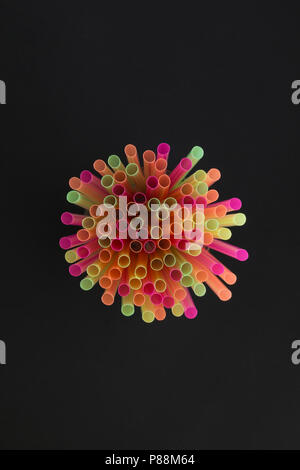 Creative view of drinking straws for party on black background in neon colors. Top view. - Stock Photo
