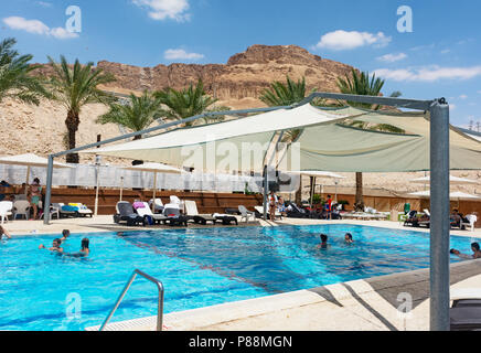 outdoor, partially shaded swimming pool at a hotel in Ein Bokek on the Dead Sea with desert mountain in the background - Stock Photo