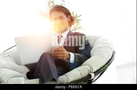 successful businessman with laptop sitting in a large comfortable armchai - Stock Photo