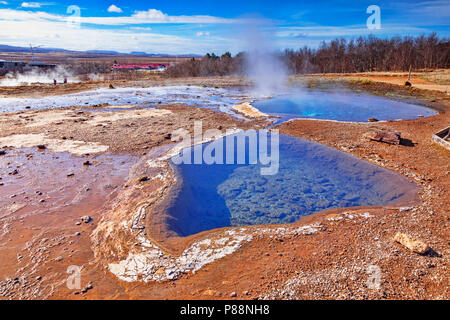 20 April 2018: Geysir, Iceland - Hot springs steaming on a fine spring day. - Stock Photo