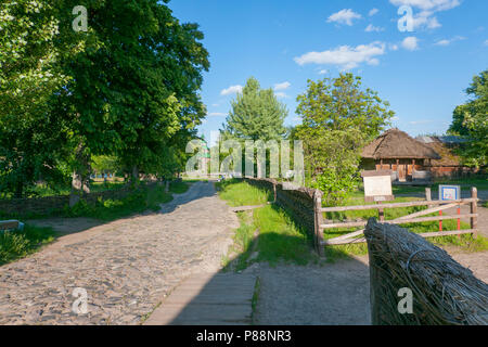 An ancient rural street with a road paved with cobblestones with wooden houses standing in courtyards fenced with a wattle fence with tall trees growi - Stock Photo