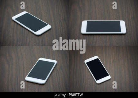 Smart phone in white color with blank screen laying on wooden table collection - Stock Photo