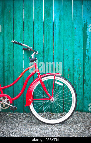 Red vintage old fashioned single speed bicycle with white tires leaning against a green painted wooden fence. British Columbia, Canada. - Stock Photo