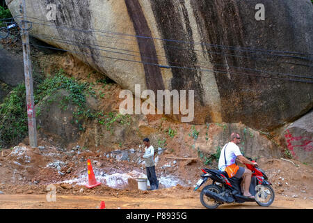 Construction Workers from Myanmar are building new roads through the jungles covering the mountains of the Thai island Koh Phangan, Thailand - Stock Photo