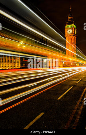 Light trails at night on Westminster Bridge Road in London with Big Ben and the Houses of Parliament lit up - Stock Photo