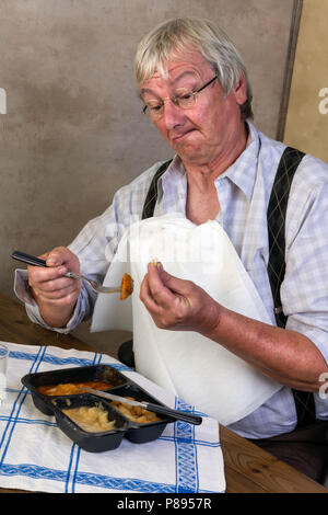 Funny elderly man breaking a tooth while eathing his tv dinner - Stock Photo