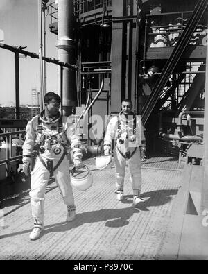 Astronauts John W. Young (left), pilot, and Virgil I. Grissom, command pilot, for the Gemini-Titan 3 flight, are shown leaving the launch pad after simulations in the Gemini-3 spacecraft. - Stock Photo