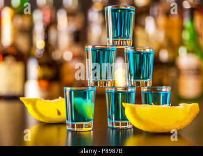 Popular blue drink shot kamikaze on the background of the bar with bottles, a refreshing drink, party night - Stock Photo