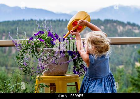 Petty, blonde, preteen girl, watering plants, outdoors.. Model Release #113 - Stock Photo