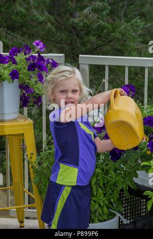 Petty, blonde, preteen girl, watering plants, outdoors.  Model Release #113 - Stock Photo