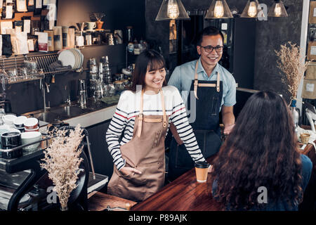 Asia barista waiter and waitress take order from customer in coffee shop,Two cafe owner writing drink order at counter bar,Food and drink business con - Stock Photo