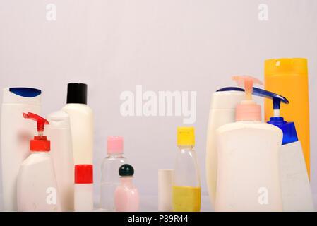 Many white plastic bottles on grey background. - Stock Photo