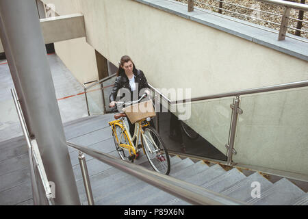 Woman with bicycle climbing up the stairs - Stock Photo