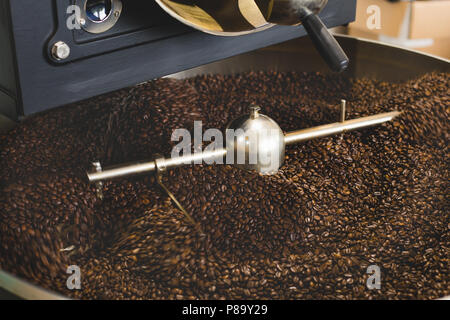 The freshly roasted coffee beans from a large coffee roaster in the cooling cylinder. Motion blur on the beans - Stock Photo