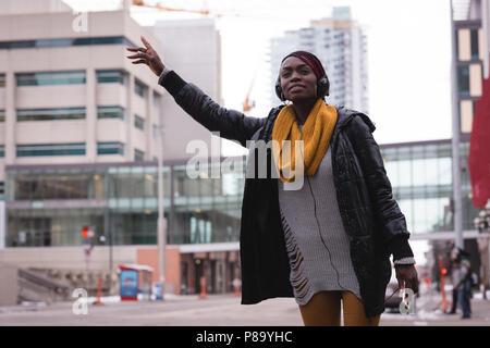 Woman hitchhiking on city street - Stock Photo