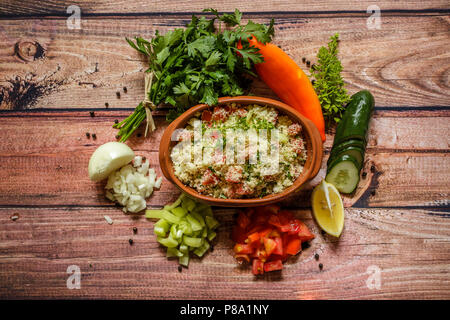 Delicious homemade vegetarian couscous with tomatoes,cucumber,pepper,onoin,lemon,parsley and basil on wooden background, close up - Stock Photo