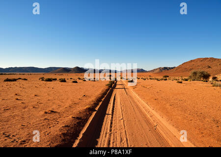 Sandtrack in the soft evening light leads through the steppe with mountains on the horizon, Tiras mountains, Namibia - Stock Photo