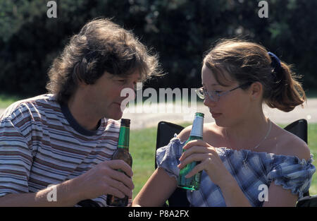 father/male adult drinking bottle of beer with teenage girl/daughter - Stock Photo