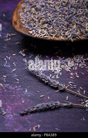 Sprigs of lavendar and scattered flowers with a bowl of dried lavender in the background. Selective focus. - Stock Photo