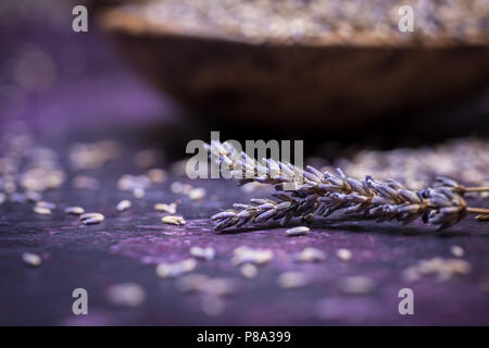 Sprigs of lavendar and scattered flowers with a bowl of dried lavender in the background. Selective focus with bokeh. - Stock Photo