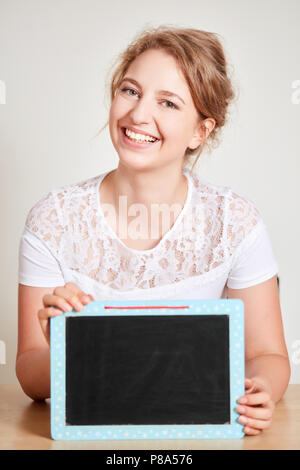 Smiling young woman is holding a blank blackboard in her hands - Stock Photo