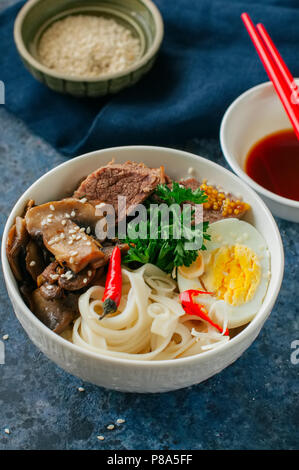 Asian food concept. Udon noodles bowl with eggs, meat, mushrooms, parsley spices and sesame seeds. - Stock Photo
