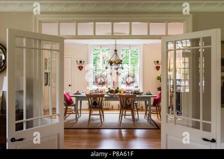 View through open double doors to dinihg room set for Christmas dinner - Stock Photo