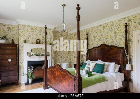 Antique wooden four-poster bed in Regency bedroom with tallboy - Stock Photo
