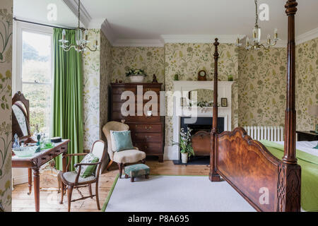 Antique wooden four-poster bed in Regency bedroom with tallboy and dressing table - Stock Photo