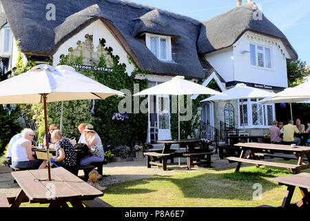 Shanklin, Isle of Wight, UK. June 24, 2018. Holidaymakers and locals enjoying a meal and drink at the Thatch Vernon cottage cafe at Shanklin on the Is - Stock Photo