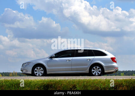 Silver car on the road against a background of green grass and blue sky . For your design - Stock Photo