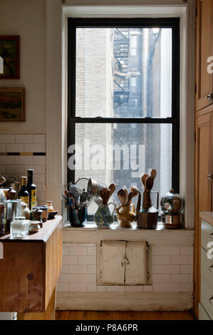 Cooking utensils stored in an assortment of jugs and pots along a New York apartment windowsill - Stock Photo