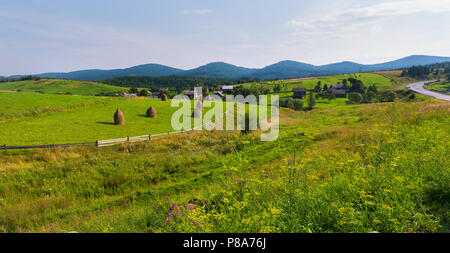 A small village on a picturesque place in the midst of the vast meadows and green mountains . For your design - Stock Photo