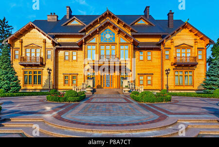 The area is laid out with beautiful patterns from the tile with a green lawn growing on it in front of the house with sheathed wood and windows of dif - Stock Photo